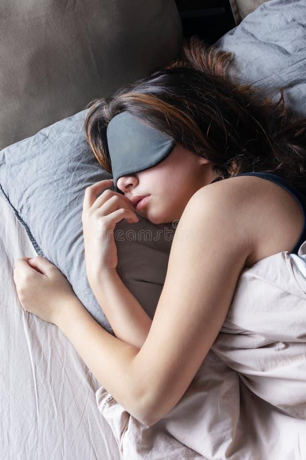 Flickan i en sömnmaskering vilar i hennes säng Härligt tonat foto arkivbild
