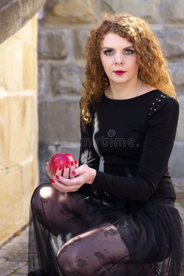 Flickan i en svart klänning med det röda äpplet royaltyfria foton