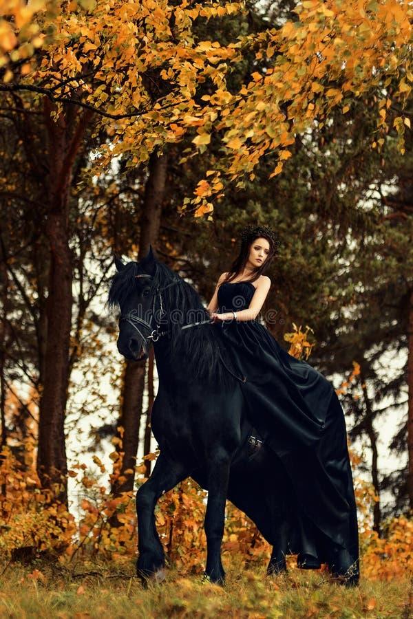 Flickan i en svart klänning och en svart tiara på en Frisianhäst rider på en magisk sagaskog royaltyfria bilder