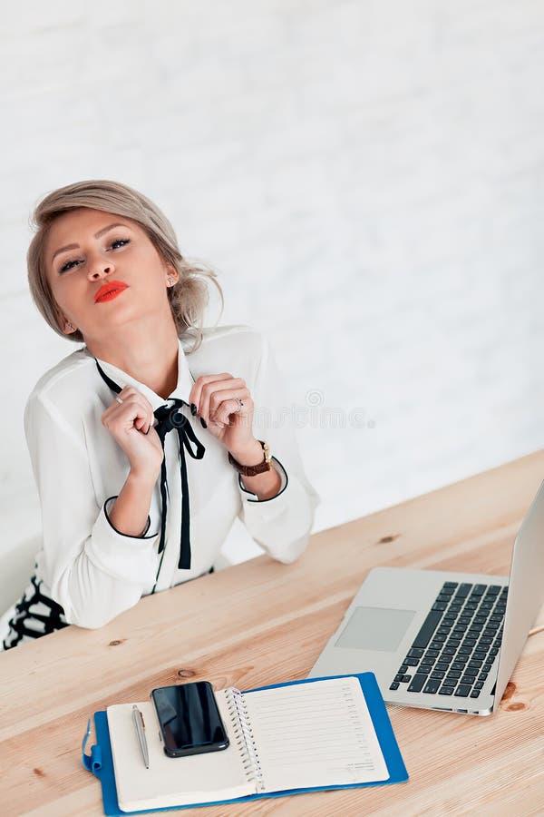 Flickan i en vit blus sitter på en tabell med en bärbar dator och överför en luftkyss royaltyfria bilder