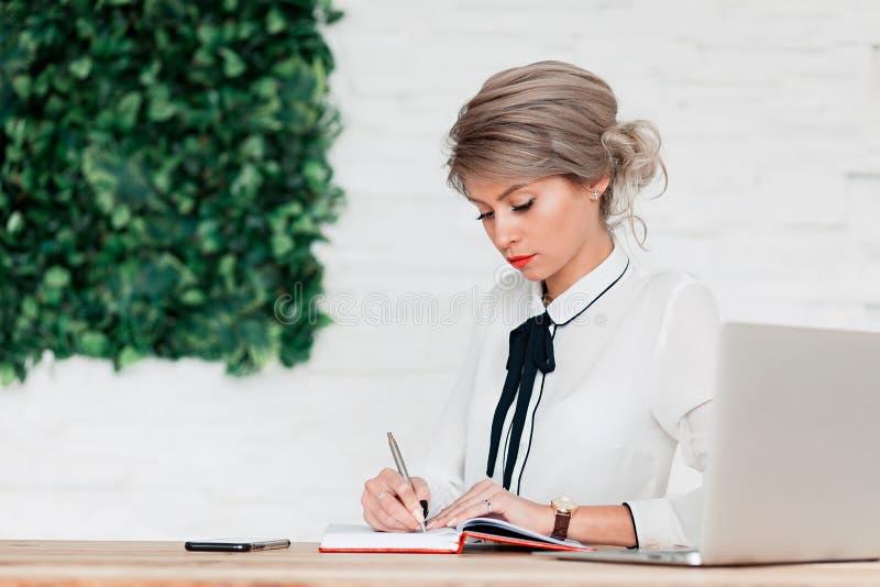 Flickan i en vit blus sitter på en tabell med en bärbar dator och skriver i en röd anteckningsbok arkivfoton