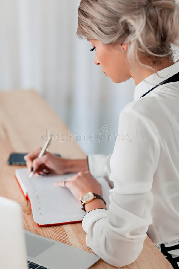 Flickan i en vit blus sitter på en tabell med en bärbar dator och skriver i en röd anteckningsbok arkivbild