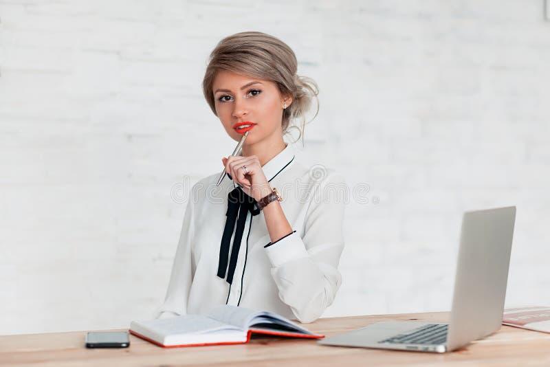 Flickan i en vit blus sitter på tabellen med en bärbar dator, en notepad och en telefon royaltyfri foto
