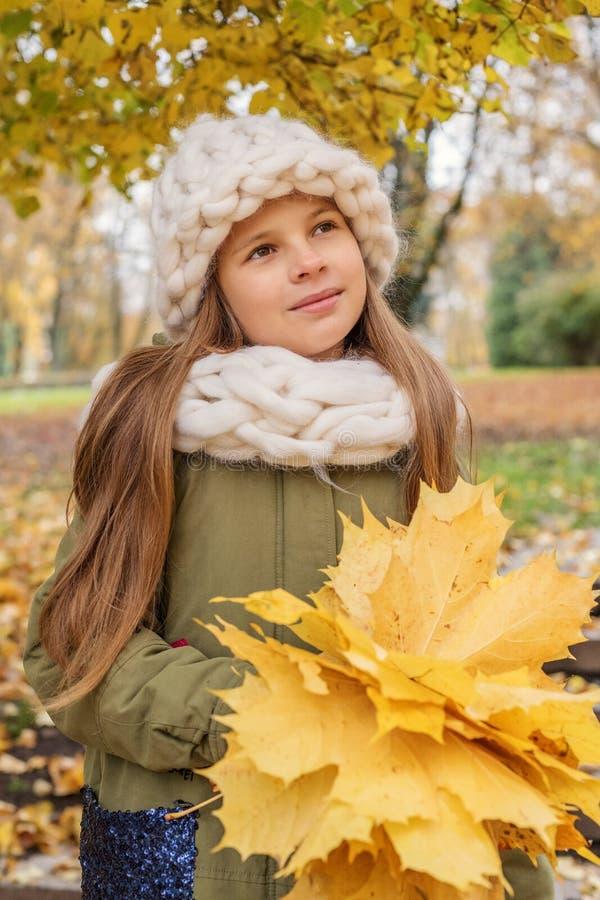 flickan i en vit halsduk och hatt med ett grovt handhandarbete med en bukett av lönnlöv står försiktigt dreamily under ett träd i royaltyfri foto