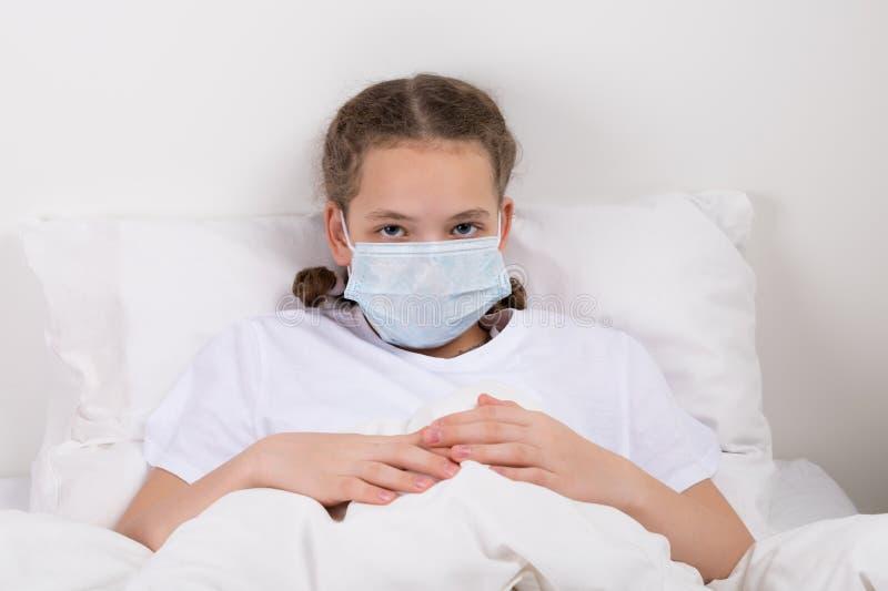 Flickan i en vit säng täckte hennes framsida med en maskering från bakterier arkivbilder