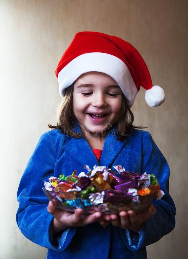 Flickan i ett jullock rymmer en maträtt med choklader royaltyfri foto