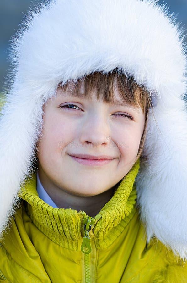 Flickan i ett lock och ett omslag blinkar ett le för öga royaltyfria foton