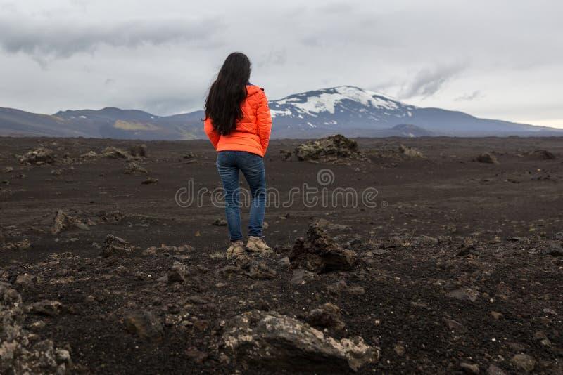 Flickan i ett orange omslag står på en sten royaltyfria foton