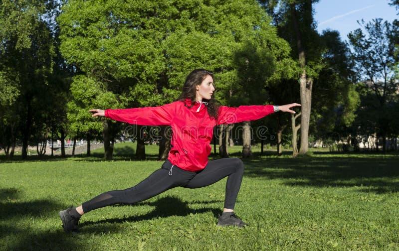 Flickan i ett rött omslag som kopplas in i sportar, yoga i, parkerar i en röjning bland träden, flickan står i poserar av en krig fotografering för bildbyråer