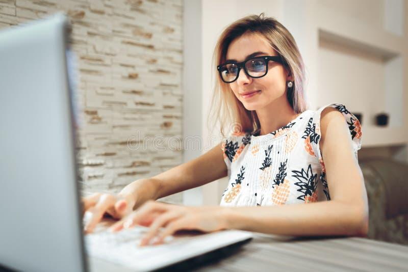 Flickan i exponeringsglas skriver på bärbara datorn royaltyfri fotografi