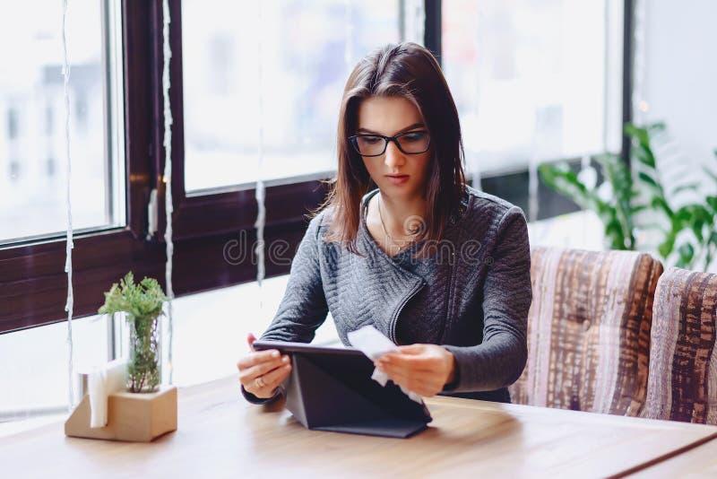 Flickan i exponeringsglas torkar minnestavlaskärmen på tabellclosupen royaltyfria bilder