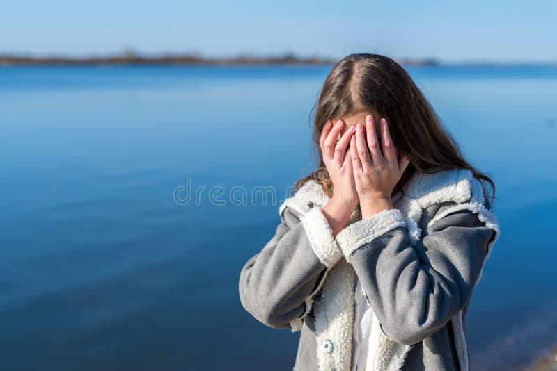 Flickan i fårskinnlaget gråter på flodbanken arkivbilder