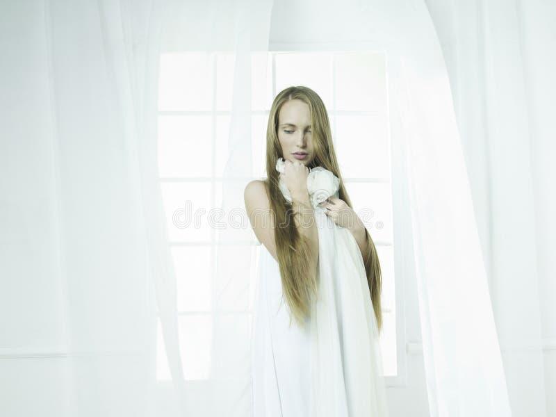 Flickan i fönstret royaltyfri foto