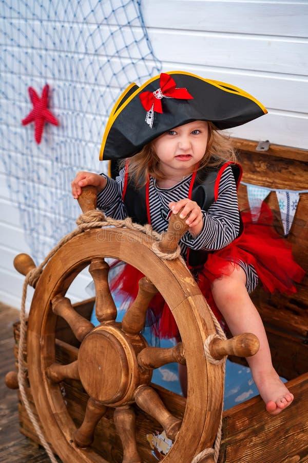 Flickan i form av piratkopierar på rodern royaltyfri foto
