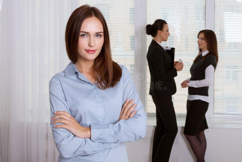 Flickan i formell kläder står i förgrunden arkivbild