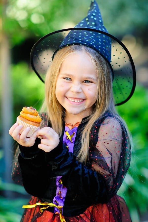 Flickan i häxadräkt äter muffin på allhelgonaafton royaltyfria foton