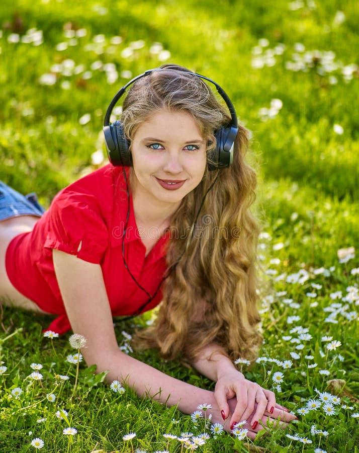Flickan i hörlurar fångar rytmmusik på grönt gräs arkivbild