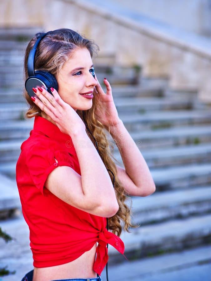 Flickan i h?rlurar lyssnar till musik som g?r ner trappa arkivfoton