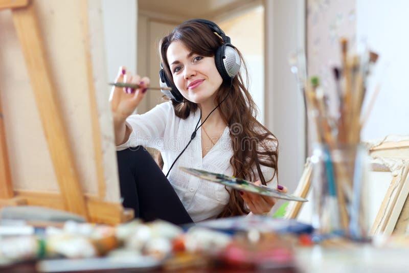 Flickan i hörlurar målar på kanfas i seminarium fotografering för bildbyråer