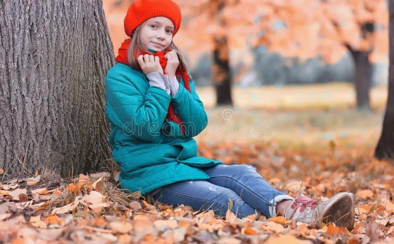 Flickan i höststad parkerar i bladnedgång Unga härliga moderwi arkivbild