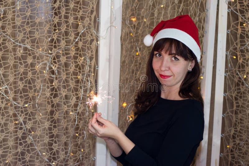 Flickan i hatten av Santa Claus med ett tomtebloss royaltyfria foton