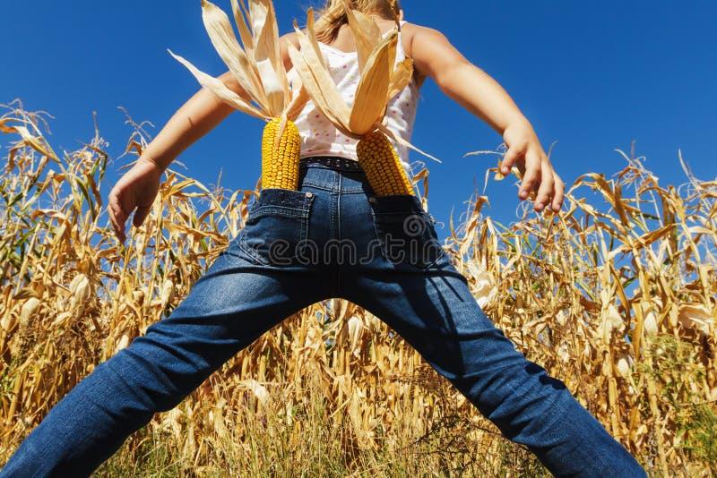Flickan i jeans på ett havrefält royaltyfria bilder