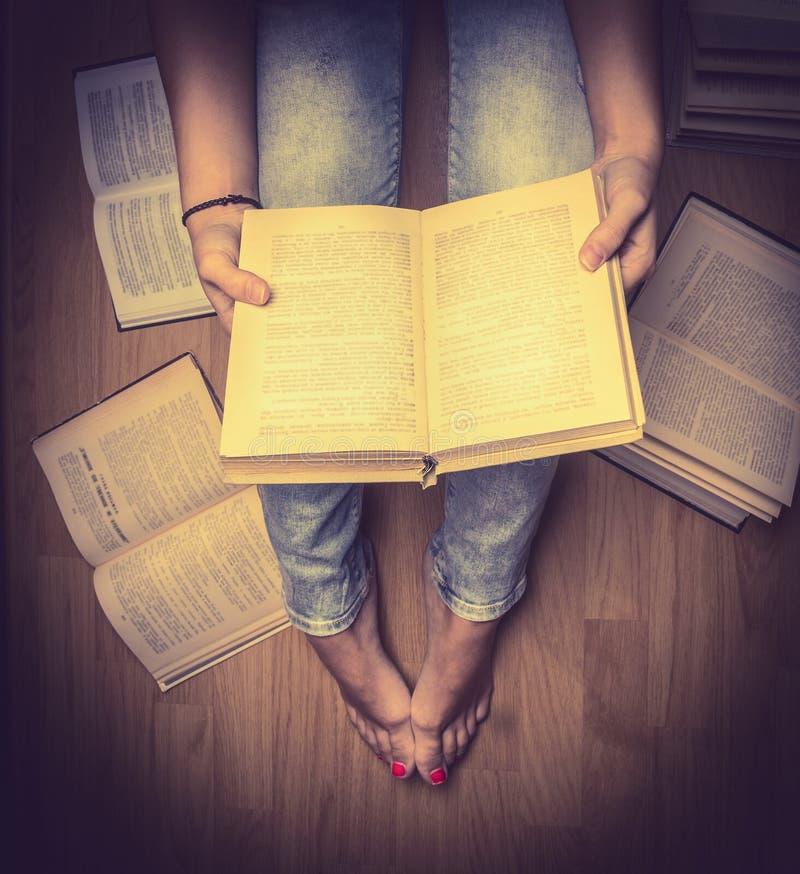 Flickan i jeans som rymmer ett boksammanträde på golvet, böcker som ligger runt om henne, student som lär läs- slut för studie up royaltyfri bild
