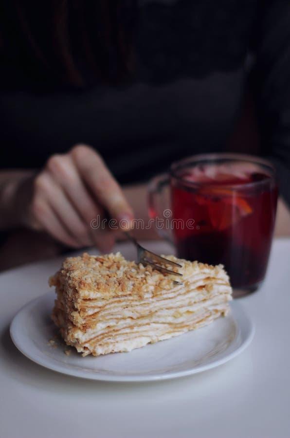 Flickan i kafét äter en läcker kaka arkivbilder