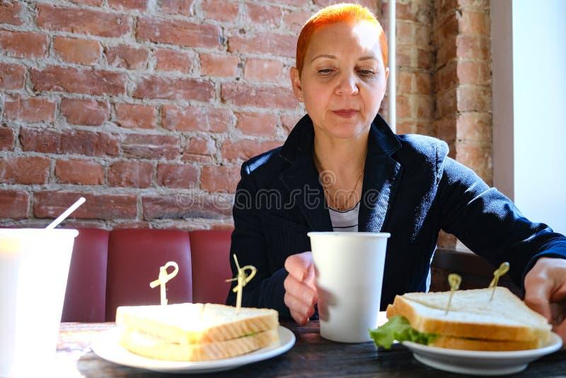 Flickan i kafét som dricker en latte som äter en smörgås Skela i solljuset Solen från fönsterskenen på framsidan arkivbild
