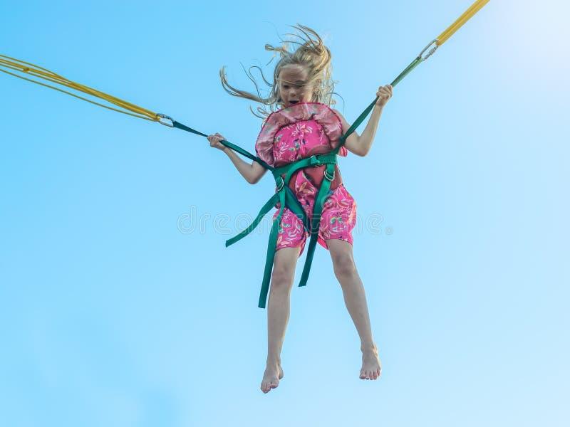 Flickan i klänningen flyger upp med hjälpen av sträckning av remmar mot den blåa himlen royaltyfria foton