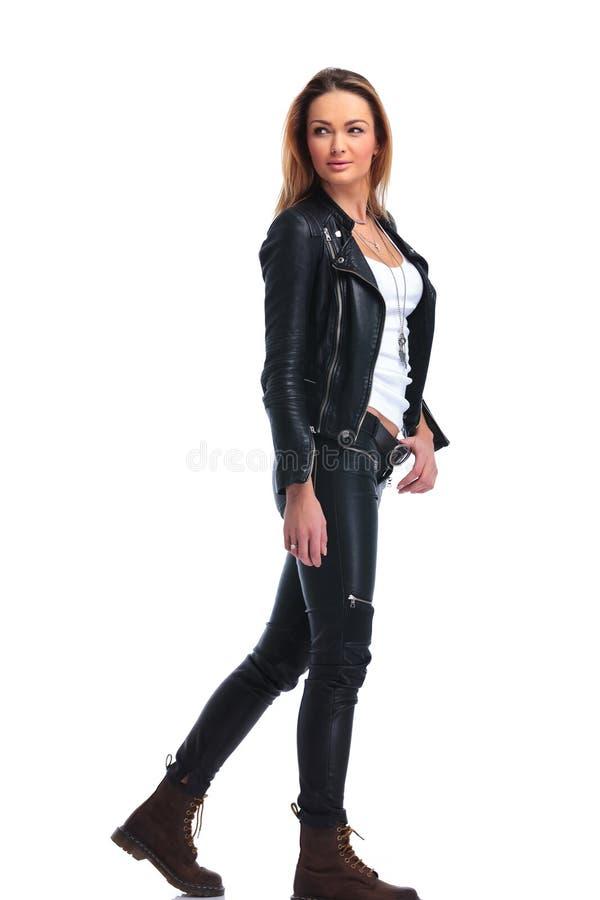 Flickan i läderomslag poserar att gå i studiobakgrund medan l fotografering för bildbyråer