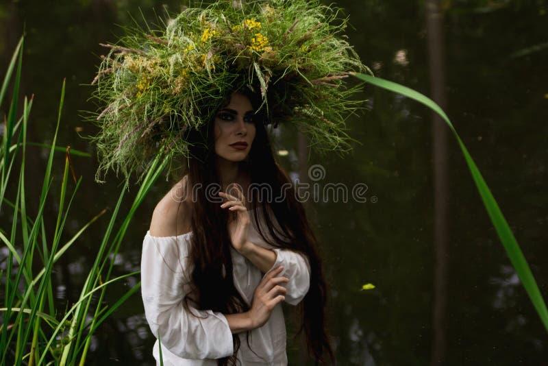 Flickan i lång klänning och krans doppar in i floden arkivfoton