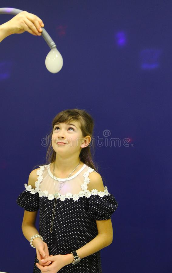 Flickan i laboratoriumet ser en boll av vätskegasformigt grundämne och tvål royaltyfri foto