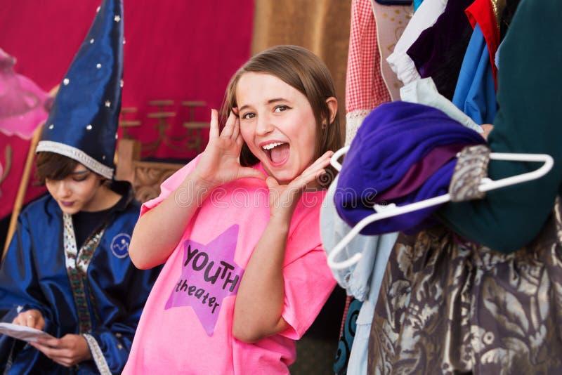 Flickan i loge poserar med händer vid framsidan royaltyfri fotografi