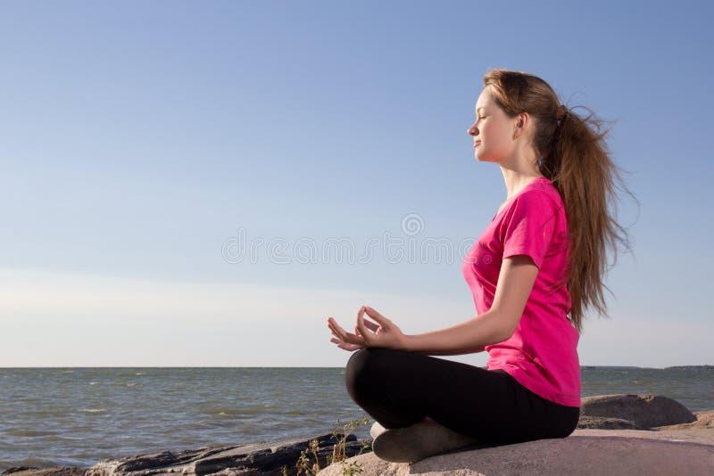 Flickan i lotusblomma poserar att sitta nära havet royaltyfri foto