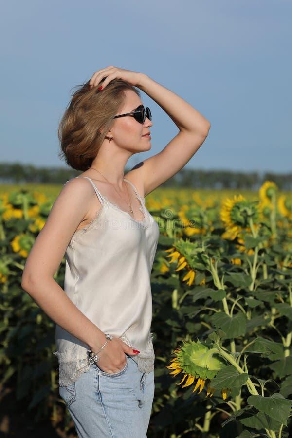 Flickan i mörka exponeringsglas går på en solnedgång på det härliga fältet av de blomstra solrosorna arkivbilder