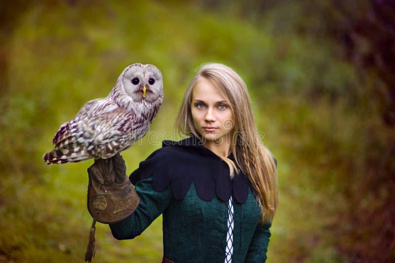 Flickan i medeltida klänning rymmer en uggla på hennes arm royaltyfri foto