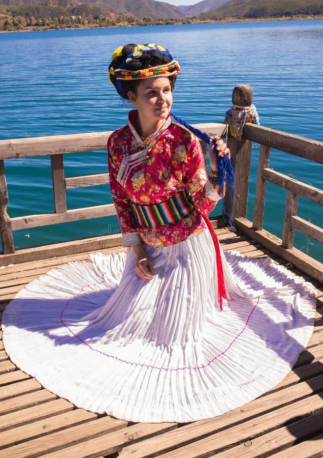 Flickan i nationell klänning på sjön arkivfoto