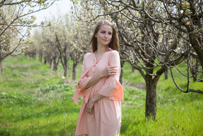 Flickan i persikaklänning går vid en blommande trädgård fotografering för bildbyråer