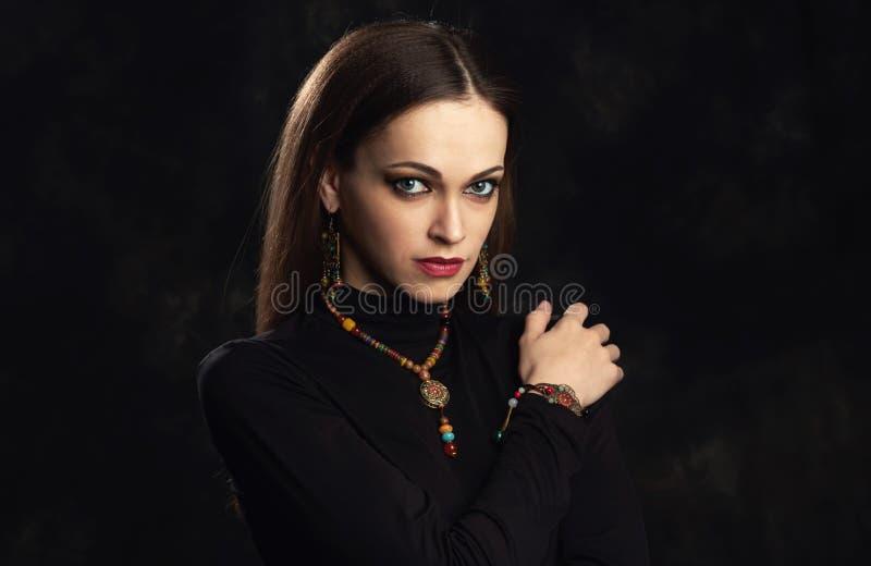 Flickan i person som tillhör en etnisk minoritet stenar halsbandet och örhängen arkivbild