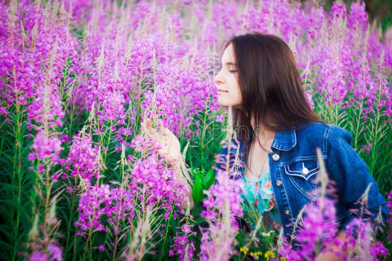 Flickan i profil på en bakgrund av lilor blommar ängar med ett leende som ser blommorna arkivfoto