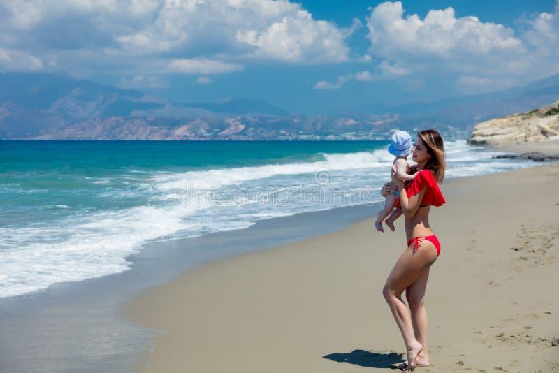 Flickan i röd bikini och behandla som ett barn på den Tympaki stranden arkivfoton