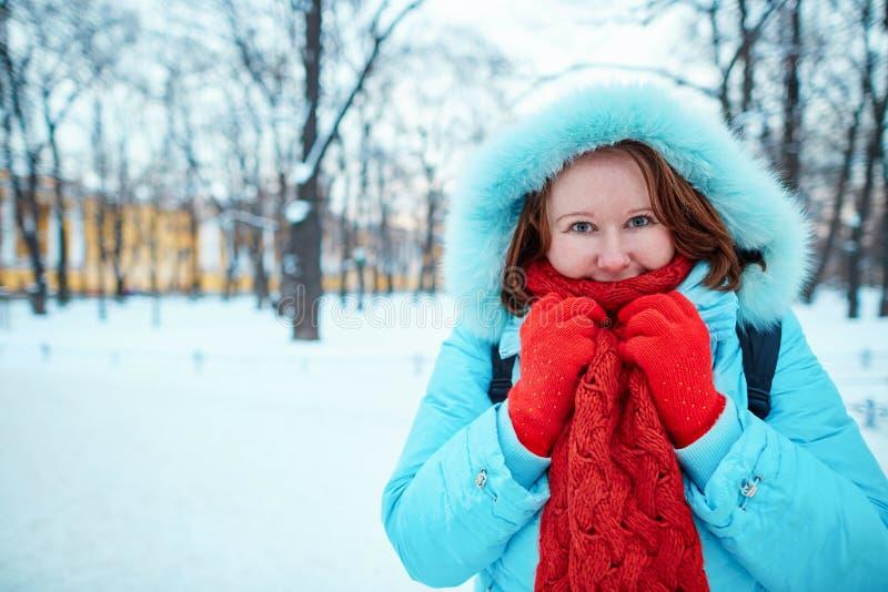 Flickan i röd halsduk parkerar in på en kall vinterdag royaltyfri fotografi