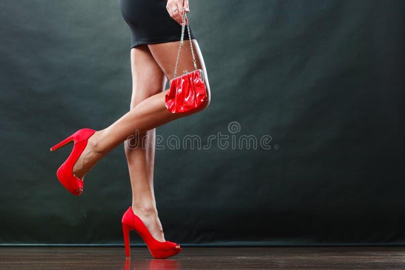 Flickan i röda broddade skor för svart kort klänning rymmer handväskan royaltyfri bild