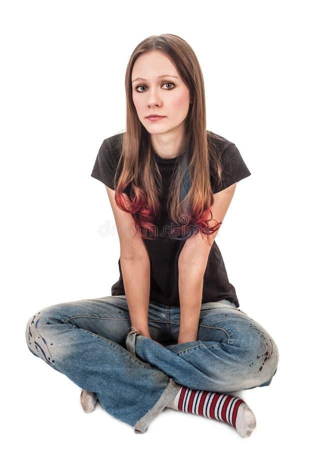 Flickan i randiga sockor sitter på däcka med hans lägger benen på ryggen crosse arkivbild