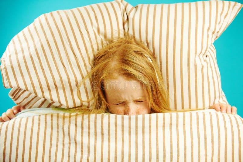 Flickan i säng med skräck stängde henne ögon som angicks, ser mardrömmar som var rädda att få ut filt från under, den bästa sikte royaltyfria bilder
