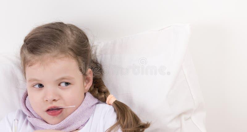 Flickan i säng tar medicin och blicken på rätten, stället för inskrift arkivbild