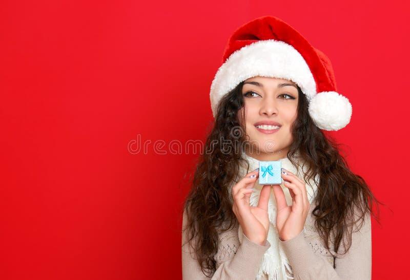 Flickan i santa hattstående med den lilla gåvaasken som poserar på bakgrund för röd färg, jul semestrar begrepp, lyckligt och sin arkivfoton