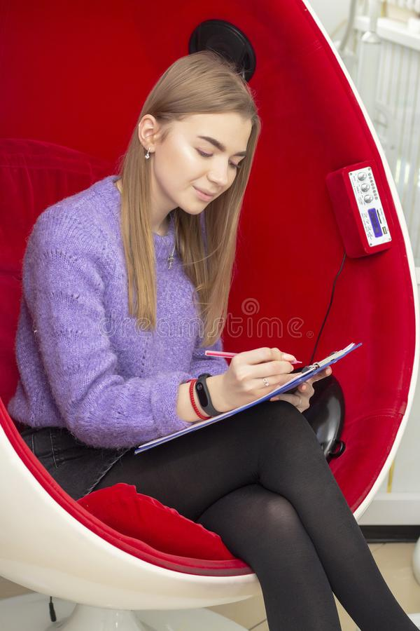 Flickan i skönhetmottagningsrum läser och undertecknar ett underhållsavtal arkivbilder