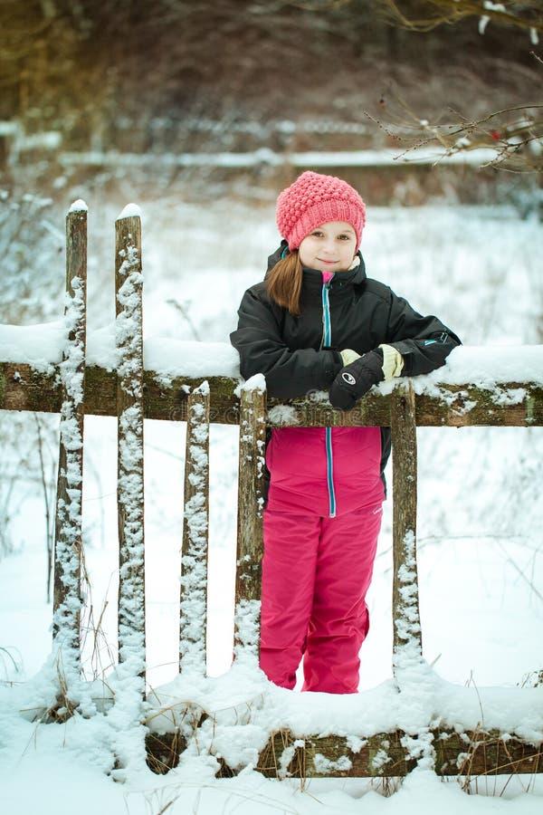 Flickan i skidar dräkten i vinterskogen royaltyfri fotografi